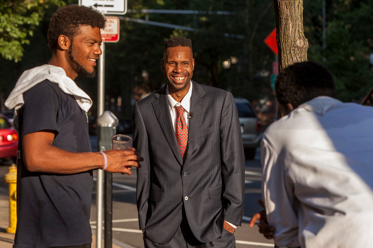 Corey Menafee, 38, center, a New Haven, Connecticut resident talks with former colleague near Calhoun College at Yale University where, on June 13, 2016 he used a broom to break a panel of stained glass dipicting slaves picking cotton. This was the first time he had contact with his former colleagues since Yale University police arrested Menafee and charged him with reckless endangerment and felony mischief. One of his former coleagues compared him to Rosa Parks. He quickly disagreed, an action that alligns with his public statements he regrets breaking private property and doesn't condone violence over discourse. His case is pending and his next Court Date is July 26, 2016. Update: Mr. Menafee is in negotiations with Yale University and may rescind his resignation and return to work. If he takes the offer he'll be working in a new dinning hall, not the one at Calhoun College. Yale has agreed to scour the campus for offensive depictions of slaves and remove them from public view to preserve them as historic artifacts. The exact terms of the offer are not yet clear. (Image by Johnathon Henninger)