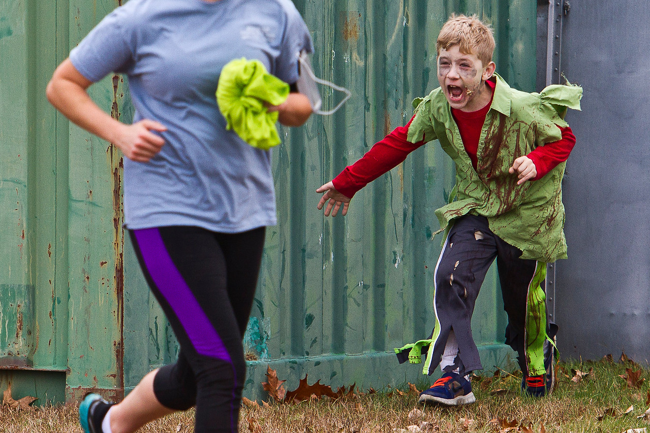 "Dawn Henry of Palmer, MA flees from Gabe Post who was hiding behind a shipping container during the second annual, ""Run for Your Lives Zombie Run,"" a program started last year by Sydney Nash, a now Freshman at Fermi High School. Volunteers dressed in zombie garb and chased runners."