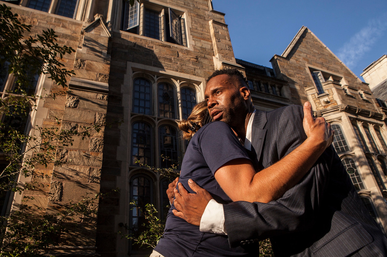 Corey Menafee, 38, a New Haven, Connecticut resident hugs a former colleague near the Calhoun College at Yale University. He was there to pose for a portrait under the panel of stained glass he broke with a broom on June 13, 2016. Colleagues saw him and offered their support and hugs. It was the first time he had contact with his former workers since Yale University police arrested Menafee and charged him with reckless endangerment and felony mischief after breaking the stained glass panel. One of his former coleagues compared him to Rosa Parks. He quickly disagreed, an action that alligns with his public statements he regrets breaking private property and doesn't condone violence over discourse. His case is pending and his next Court Date is July 26, 2016. Update: Mr. Menafee is in negotiations with Yale University and may rescind his resignation and return to work. If he takes the offer he'll be working in a new dinning hall, not the one at Calhoun College. Yale has agreed to scour the campus for offensive depictions of slaves to remove them from public view and preserve them as historic artifacts. The exact terms of the offer are not yet clear. (Image by Johnathon Henninger)