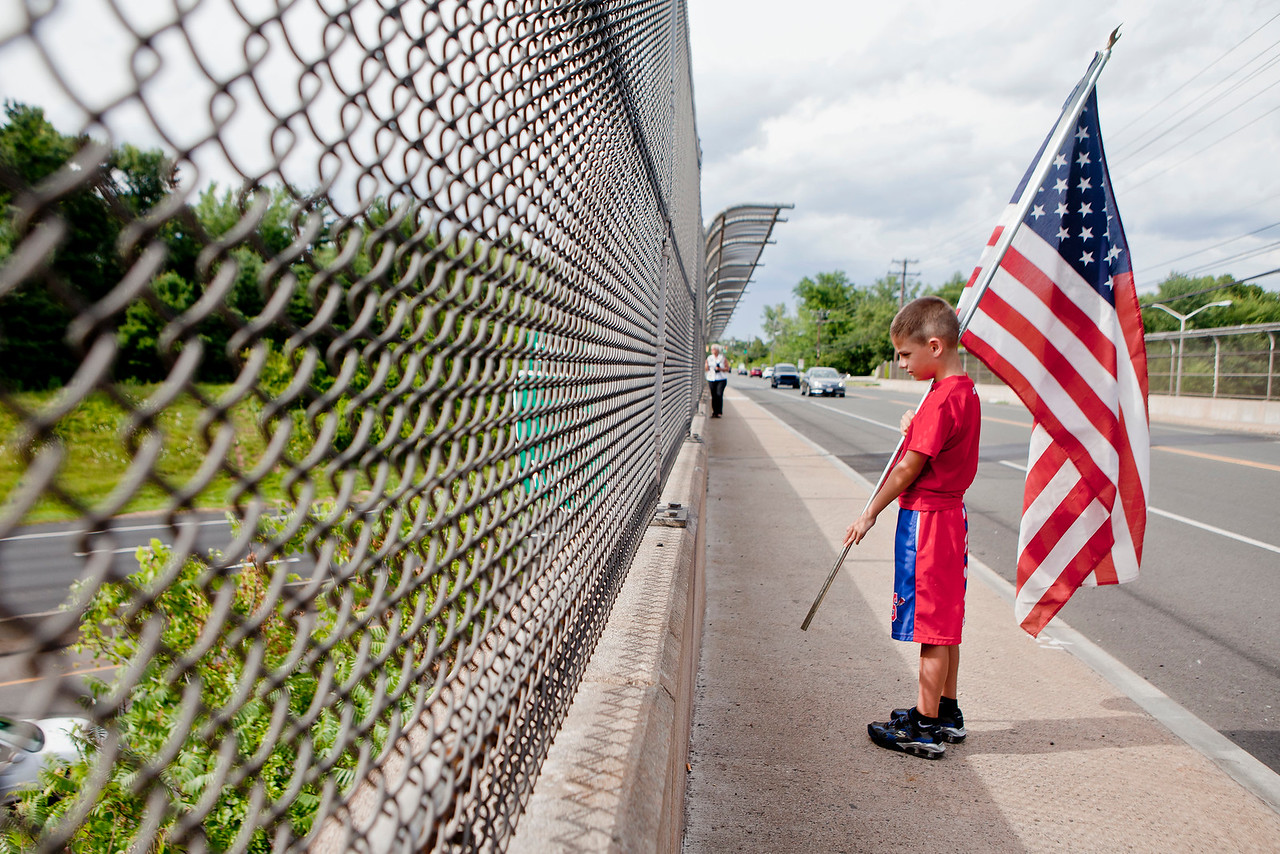 Billy Marinella, 8, stands on the King Street overpass in Enfield waiting for the casket carrying the body of Marine Thomas Sullivan to pass by.