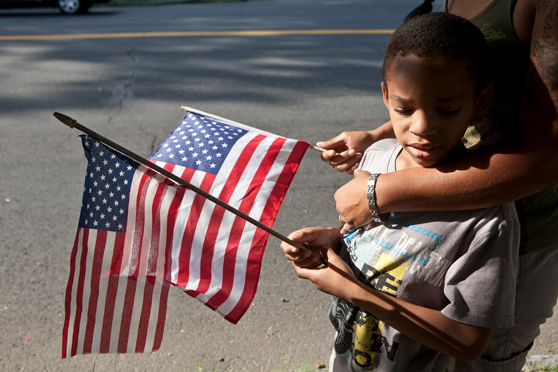 "Jessie Jones, 7, a Springfield, MA resident stands holding an Amerian Flag in the arms of this mother, Virginia Baily who's father is a Marine. ""I come from a long line of Marines. I'm here to pay respects. They can take him [Thomas Sullivan] but they can't take what he stood for."