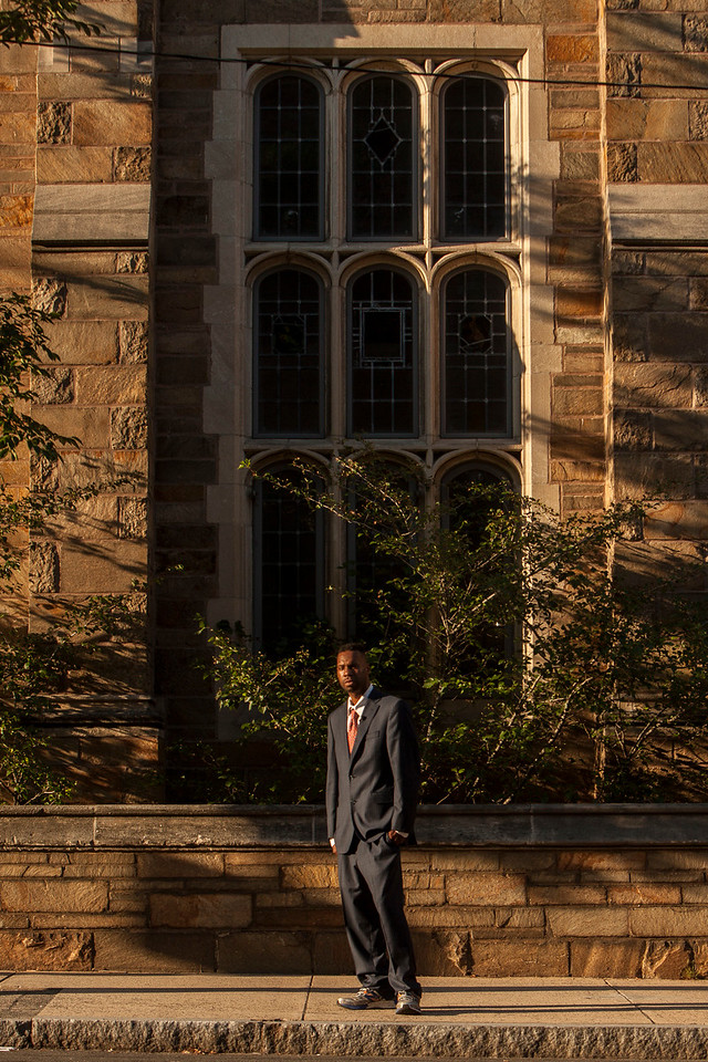 Corey Menafee, 38, a New Haven, Connecticut resident stands beneath a window at Calhoun College at Yale University. On June 13, 2016 he stood on a table and broke the stained glass window. It contained the image of two slaves picking cotton. Colleagues saw him standing outside and offered their support in the form of hugs. It was the first time he had contact with his former colleagues since Yale University police arrested Menafee and charged him with reckless endangerment and felony mischief after breaking the stained glass panel. One of his former coleagues compared him to Rosa Parks. He quickly disagreed, waving off comment, an action that alligns with his public statements he regrets breaking private property and doesn't condone violence over discourse. His case is pending and his next court date is July 26, 2016 in which Yale is expected to suggest the charges be nullified. Update: Mr. Menafee is in negotiations with Yale University and may rescind his resignation and return to work. If he takes the offer he'll be working in a new dinning hall, not the one at Calhoun College. Yale has agreed to scour the campus for offensive depictions of slaves and remove them from public view to preserve them as historic artifacts. The exact terms of the offer are not yet clear. (Image by Johnathon Henninger)