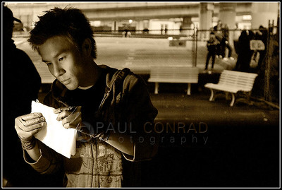 © Paul Conrad/Pablo Conrad Photography - Tommy Nguyen of the Vietnamese Christian Community Church uses a portable light to fold napkins as volunteers prepare dinner for the homeless on Monday evening under Interstate 5 at James Street in downtown Seattle, Wash. Members of Discovery House, Vietnamese Christian Community Church, and others prepare food for serving to the homeless.   (© Paul Conrad/Paul Conrad Photography)