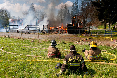 © Paul Conrad/ Pablo Conrad Photography - Several Whatcom County firefighters take a rest as they monitor a controlled training fire on Kline Street one mile east of Meridian Avenue north of Bellingham on Saturday afternoon April 12, 2014.   (© Paul Conrad/Paul Conrad Photography)