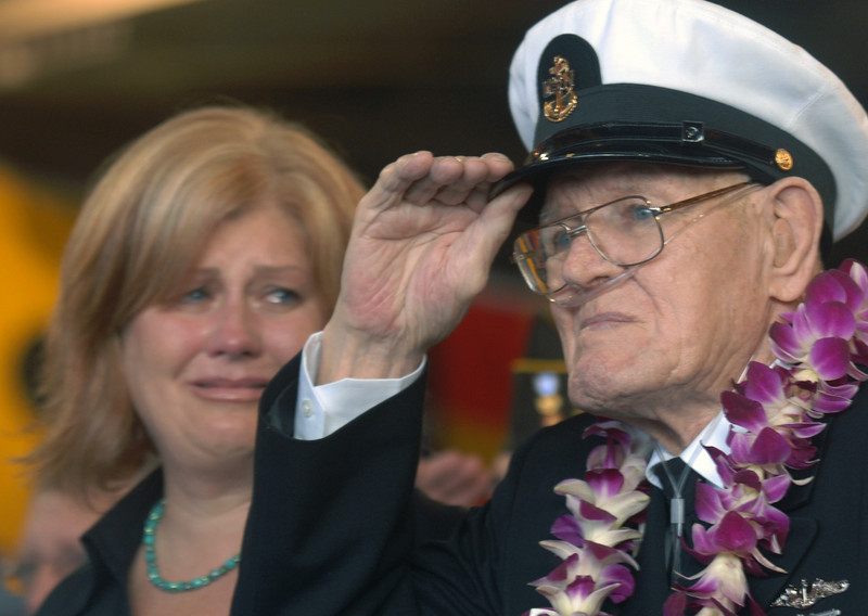 "PEARL HARBOR, HI - DECEMBER 7: Lois Deininger of San Francisco, cries as she watches her father, Pearl Harbor survivor, Edward Gaulrapp, 84, of Freeport, Illinois saluting in his chief's uniform, during the commemoration marking the 66th anniversary of Pearl Harbor attack , Friday, Dec. 7, 2007 at Pearl Harbor, Hawaii.  Gaulrapp was in the enlisted mans barracks during the attack and saw the Arizona being bombed. He was given a rifle to shoot down the incoming japanese aircraft and says ""there was no way to shoot down  planes with weapons but it made us feel better'.  (Photo by Lucy Pemoni/Getty Images)"