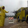 Jimmie Kia a city road worker, standing in water during a downpour, directs a firetruck through a portion of Alala Road in Kailua which had one lane closed due to flooding Thursday, Feb. 26, 2004. A potent storm system is expected to maintain the rain, high wind advisory and flood warning for several more days. (AP Photo/Lucy Pemoni)