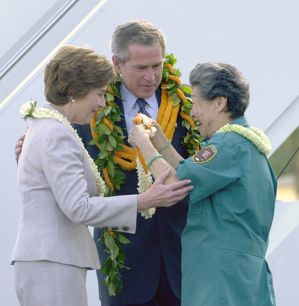 President George Bush receives a  maile (leaf) lei intertwined with ilima (orange flowers) from Hilma Chang, a Freedom Corp volunteer shortly after Pres. Bush arrived at Hickem Air Force Base outside of Honolulu, Hawaii, Thursday October 23, 2003.  Chang has been a volunteer for many years at the U.S.S. MemoriaL was a child during the attacks on Pearl Harbor and  witnessed  the bombings and ensuing marshal law and blackouts. REUTERS/Lucy Pemoni