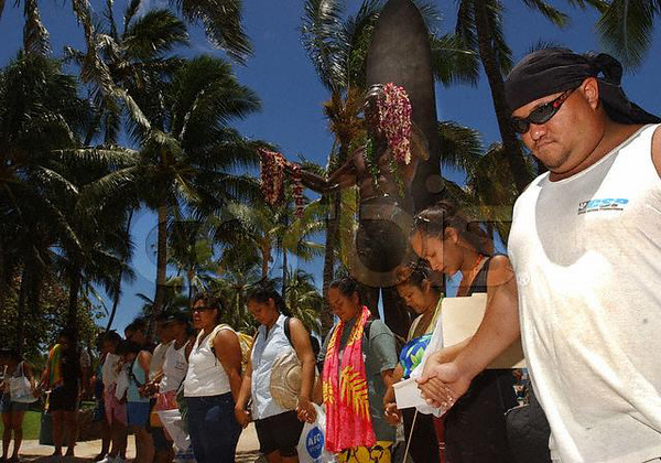 Original caption: Wilsam Keahaaina, 30, (far right) of Honolulu and Kahuanani Kalua, 25, of Waipahu, hold hands and pray with about a hundred other native Hawaiian language teachers, July 22, 2003 on Waikiki Beach in Honolulu. Only a few years ago the Hawaiian language was a rare form of communication but recently, with support from native speakers like the members of the 'Aha Puanna Leo' group, cultural programs and instruction are keeping alive the Hawaiian language and culture for preschool children and adults alike throughout the islands. Picture taken July 22, 2003. REUTERS/Lucy Pemoni
