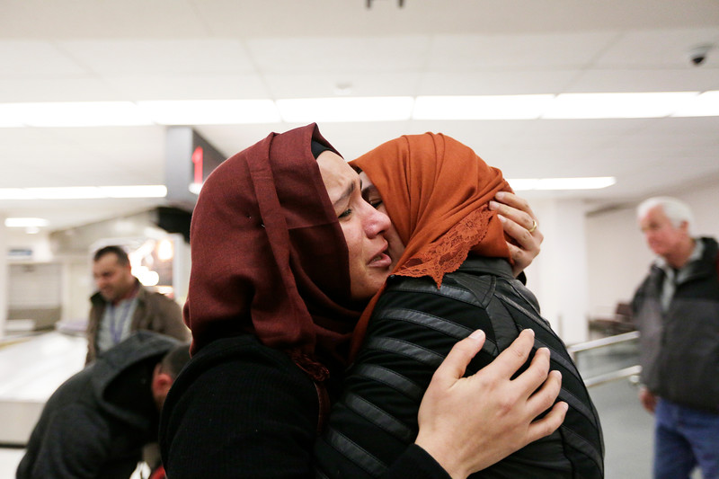 Nadia Amzuabidi, left, hugs her sister Athraa Hachim Jameel, a refugee from Iraq who arrived on a flight, at the Spokane International Airport in Spokane, Wash., Saturday, Feb. 11, 2017. (Young Kwak/The Inlander)
