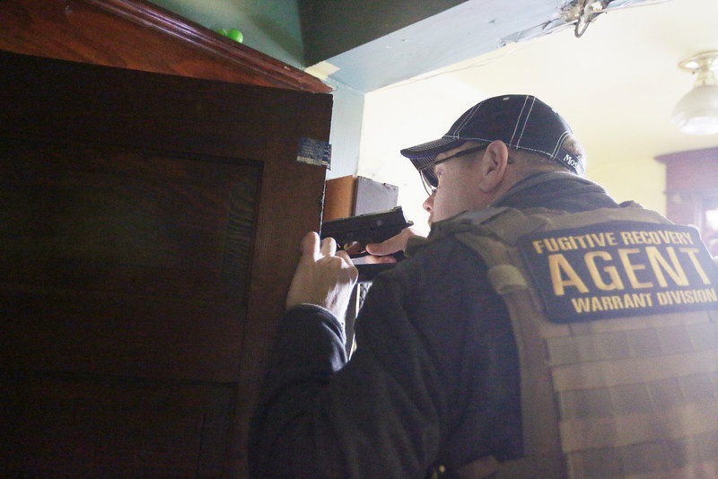 Bail Enforcement and Fugitive Recovery Agent Scott G. draws his firearm when he discovers a person hiding in a room at a house that Zane Regan, not pictured, who is wanted for a controlled substance felony charge, is known to frequent, Monday, Feb. 1, 2016, in Spokane, Wash. (Young Kwak/Pacific Northwest Inlander)
