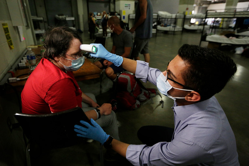 Mohammad Keshtkar, right, a volunteer with the Spokane Regional Health District, checks Amanda Stockton's temperature while conducting a COVID-19 screening at the Spokane Veterans Memorial Arena, which is a temporary shelter for homeless people operated by the Guardians Foundation, in Spokane, Wash., Monday, July 13, 2020. A team with the health district screens each person at the shelter for COVID-19 daily. (Young Kwak/The Inlander)