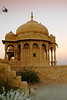 Sunset point at Vyas Chatri, Jaisalmer, Rajasthan, India is quite famous. There are two groups of Cenotaphs (Vyas Chhattri for Brahmins and Bada Bagh for the royal families) situated at the end of town giving a spectacular view of the Jaisalmer Fort and the Sunset opposite it. The Chatris (umbrellas) have fine carvings and a royal feel to it.