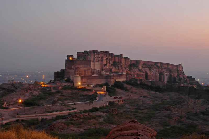 Evening light of the setting Sun on Mehrangarh Fort, Jodhpur. The Mehrangarh Fort is spread over an area of 5 sq. km in the heart of the city. The fort has seven gates  Seen in the foreground are tourist buses that bring lots of visitors daily to the Fort. Jodhpur, Rajasthan, Western India.