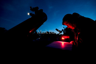 "Amy Cantu of Ann Arbor looks at a star chart next to her 8"" telescope at Peach Mountain near Dexter, Michigan in June of 2010.  The moon is visible near the telescope's eyepiece."