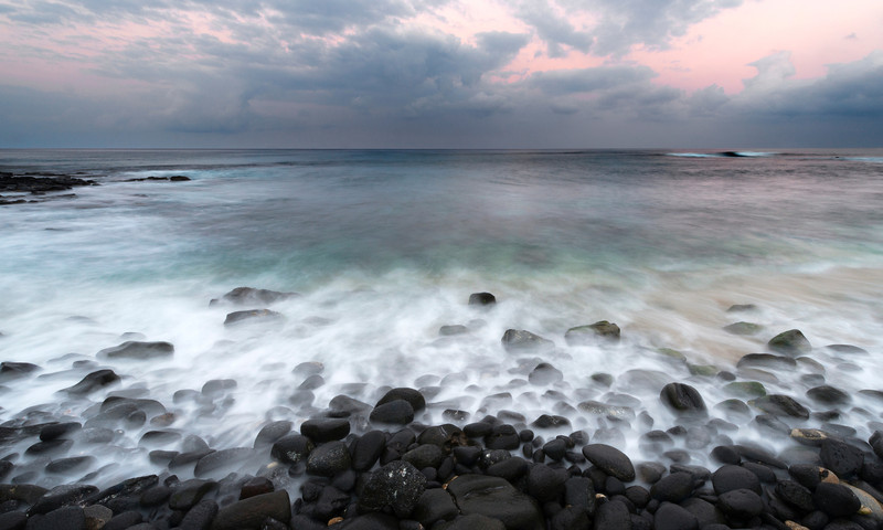 Whispering Stones, Kona Coast - Hawaii  With a long exposure, the movement of the waves creates a ghostly mist around the water-rounded black lava rocks of the Kona Coast.