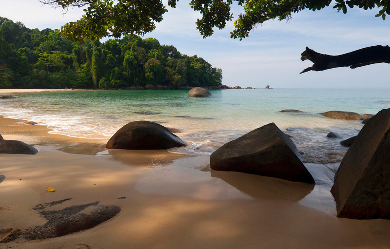 """Little Jerry Beach, Koh Lak - Thailand  On the crude scrap of paper that was called a 'map' this beach was noted as """"secret beach"""". And so we hiked; through the rain forest, along jungle cliffs webbed with vines, up and down muddy troughs of leaf litter, in the darkness of an occlusive green canopy, through the webs of gigantic Golden Orb spiders (5 inch legspan), to finally emerge on this pristine sand beach. After hours of profuse sweating, we walked into the light and laid in the sand - only to notice a maintained trail coming down through the forest behind us, from the highway, and a bamboo shack selling ice cream and soda. Stupid map."""