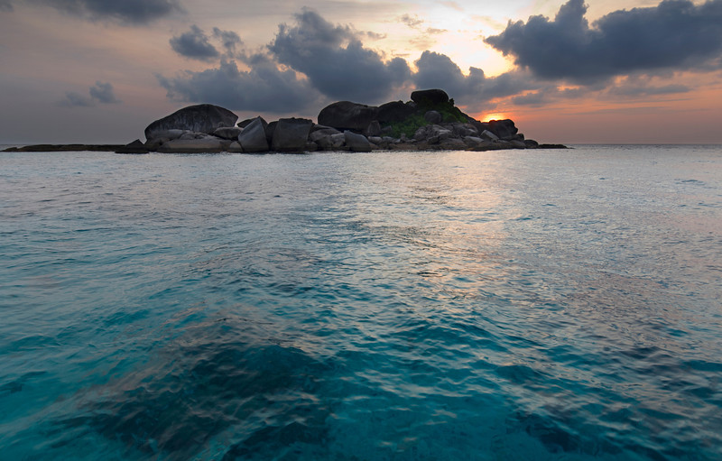 Similan Sunrise - Thailand<br /> <br /> Sunrise over the tiny Islet of Similan #6. Although not large enough to posses a white sand beach, this tiny granite outcropping is surrounded with lively reefs filled with hundreds of species of tropical fish, soft and hard corals, octopus and the occasional larger pelagic.