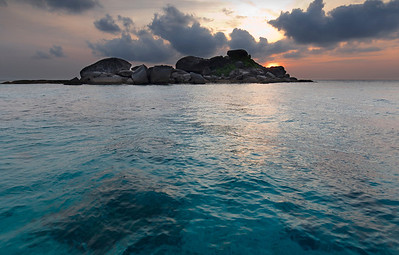 Similan Sunrise - Thailand  Sunrise over the tiny Islet of Similan #6. Although not large enough to posses a white sand beach, this tiny granite outcropping is surrounded with lively reefs filled with hundreds of species of tropical fish, soft and hard corals, octopus and the occasional larger pelagic.