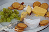 A cheese platter with grapes which has been half eaten