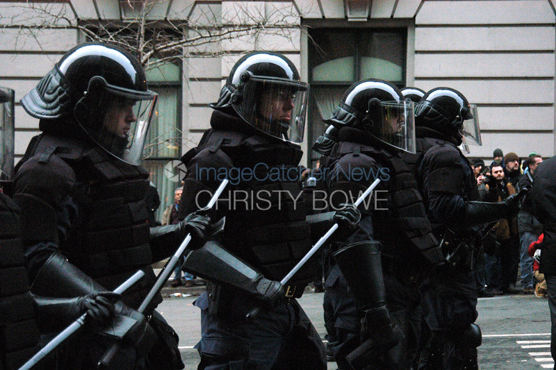 Police in riot gear stand in waiting as the Inaugural Parade begins.