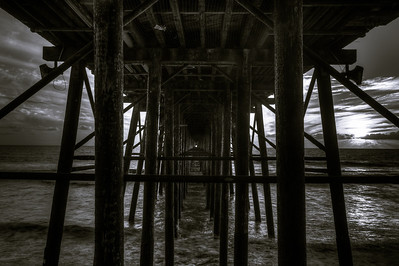 My most recent rendition of my favorite picture spot. Under the pier in Oceanside. 3 capture HDR on a tripod... it could have been a gorrila pod because my tripod was balancing on one of the cross beams and it's feet were dangling since it was all boulders underneath. I shot it at about 30mm. I have the color version as well, and it is a gorgeous sunset, but this black and white seems to fit better. It is dirty, rich, grimey, and ominous feeling.