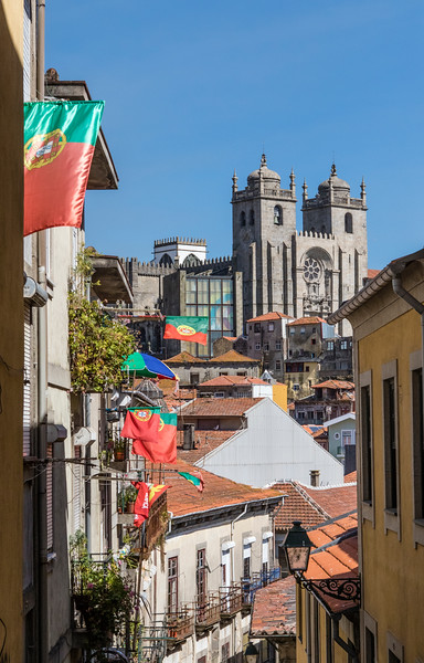 PORTO. VIEW AT THE SE CATHEDRAL SEEN FROM A SMALL STREET WITH PORTUGUESE FLAGS.