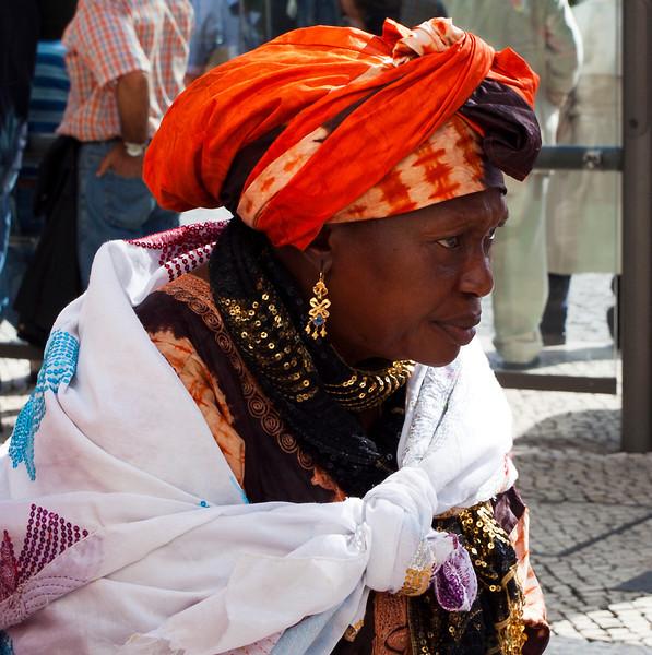 LISBON. LISBOA. ROSSIO. PRACA DOM PEDRO IV. AFRICAN WOMAN IN COLOURFUL DRESS.