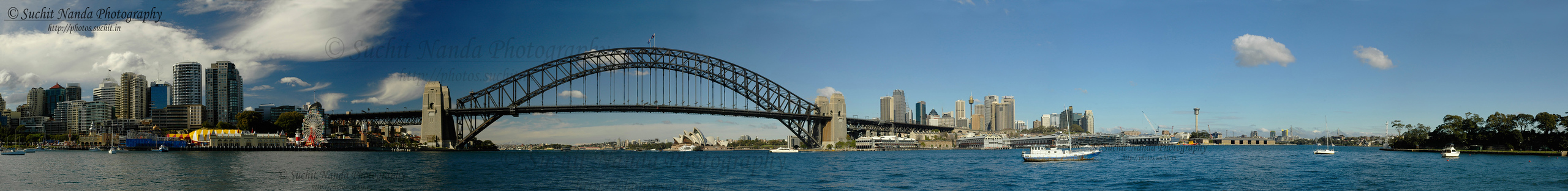 Panoramic image of the Sydney Harbour Bridge. This steel arch bridge across Sydney Harbour was formally opened in March 1932 and the bridge was the city's tallest structure until 1967. It carries rail, vehicular, and pedestrian traffic between the Sydney central business district (CBD) and the North Shore. From the bridge one gets a nice view of Sydney's Opera House.  According to Guinness World Records, it is the world's widest long-span bridge and its tallest steel arch bridge.   See large sized:  http://photos.suchit.in/photos/311127829_AU8cN-O.jpg
