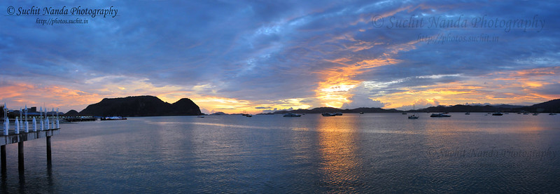 "Panoramic image showing the lovely sunset at Eagle Square / Dataran Lang is Langkawi's most prominent landmark for visitors arriving by sea and also a place visited by others. Situated near the Kuah jetty, the main attraction of the square is the magnificent statue of the reddish brown eagle majestically poised for flight. According to local folklore, the name Langkawi itself is derived from- the eagle or ""helang"". In old Malay, ""kawi"" denotes reddish brown - hence, Langkawi means reddish brown eagle!"