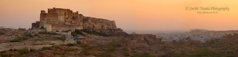 Jodhpur Mehrangarh Fort at Sunset, Rajasthan, India.   http://photos.suchit.in/photos/143587748-O.jpg  Panoramic image shot of Mehrangarh Fort, Jodhpur in the evening light of the setting Sun. The Mehrangarh Fort is spread over an area of 5 sq. km in the heart of the city. The fort has seven gates  Seen in the foreground are tourist buses that bring lots of visitors daily to the Fort. Jodhpur, Rajasthan, Western India.