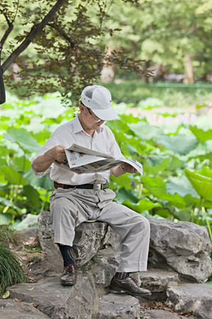 8) Man reading Newspaper on Rock