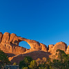 """Sunset at Skyline Arch in Arches National Park in Utah. Arches National Park contains the world's largest concentration of natural stone arches. This National Park is a red, arid desert, punctuated with oddly eroded sandstone forms such as fins, pinnacles, spires, balanced rocks, and arches. The 73,000-acre region has over 2,000 of these """"miracles of nature."""""""