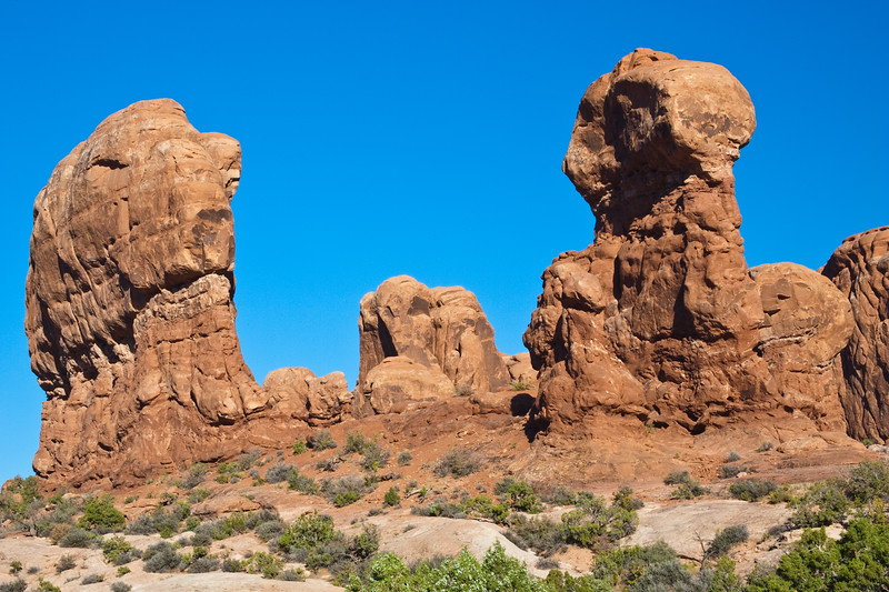 """Garden of Eden formations in Arches National Park in Utah. Arches National Park contains the world's largest concentration of natural stone arches. This National Park is a red, arid desert, punctuated with oddly eroded sandstone forms such as fins, pinnacles, spires, balanced rocks, and arches. The 73,000-acre region has over 2,000 of these """"miracles of nature."""""""