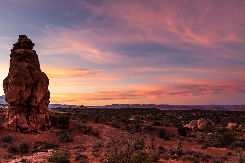 Striking colors in clouds at sunrise over sandstone formations in Arches National Park in Utah.