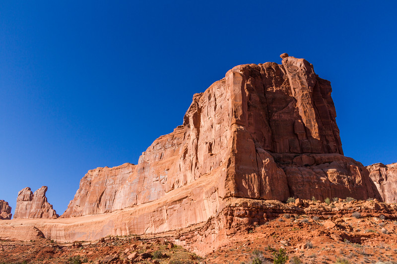 The Courthouse Towers rock formation in early morning light in Arches National Park.