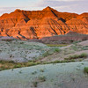 Sunrise at Badlands National Park in South Dakota. Early morning sunlight is painting light and shadows across the mountains and rock formations and grasslands in the South Dakota Badlands.
