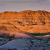 Sunrise in the Badlands National Park in South Dakota. Early morning sunlight is painting light and shadows across the mountains and rock formations and grasslands in the South Dakota Badlands.
