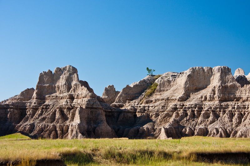 Badlands National Park in South Dakota. Early morning sunlight is painting light and shadows across the mountains and rock formations and grasslands in the South Dakota Badlands.