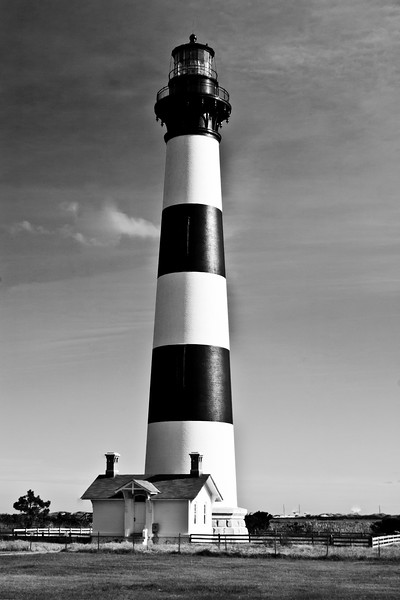Bodie Island Lighthouse on the Outer Banks of North Carolina. The current lighthouse was built in 1871 and the 164-foot tower's first-order Fresnel lens, fabricated by Barbier and Fenestre of Paris, was lit on October 1, 1872. The original lighthouse was built in 1847, but was of poor quality, and the second tower built in 1859 was destroyed in the Civil War. Bodie Island Lighthouse is still active and is now owned by the National Park Service.