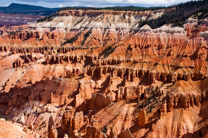 """Hoodoos and colorful cliffs at Cedar Breaks National Monument in Utah.  The Indians called Cedar Breaks the """"Circle of Painted Cliffs."""" At an elevation of 10,000 feet, Cedar Breaks is shaped like a giant coliseum dropping 2,000 feet to its floor. Carved by millions of years of erosion, Cedar Breaks displays a huge amphitheater with stone spires, columns, arches, pinnacles, and colorful canyons."""
