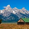 """Abandoned farm building on """"Mormon Row""""  wtih the Grand Tetons Mountain Range in the background, located in the Grand Tetons National Park in Wyoming."""