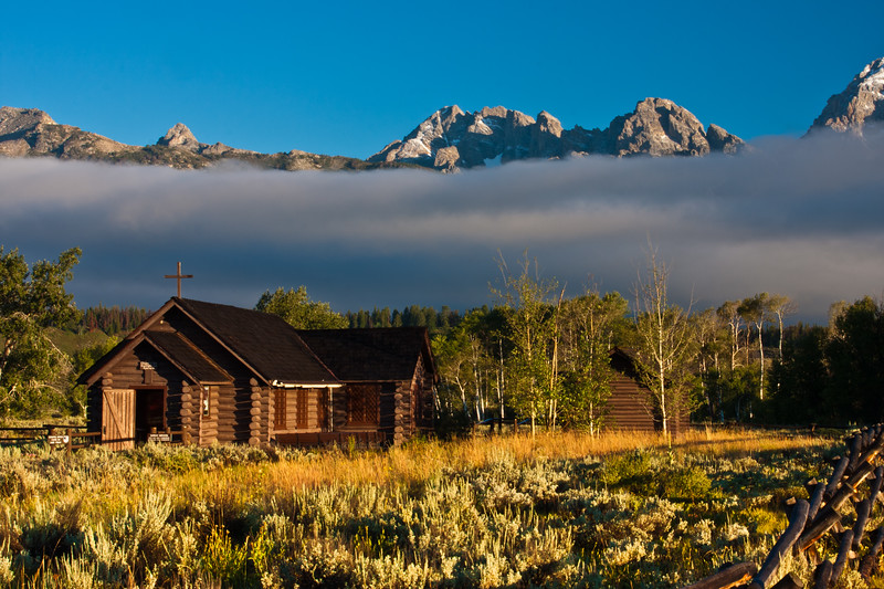 Grand Tetons Mountain Range and the Episcopal Chapel of the Transfiguration at sunrise, bathed in early morning light, in the Grand Tetons National Park in Wyoming.