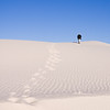 Photographer climbing Sand dunes at White Sands  National Monument in New Mexico on a cold morning in February. White Sands park is at the northern end of the Chihuahuan Desert in the mountain-ringed valley called the Tularosa Basin. Great wave-like dunes of gypsum sand cover 275 square miles of desert, the world's largest gypsum sand field.