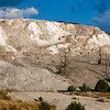 Mammoth Hot Springs in Yellowstone National Park in Wyoming. The main attraction at Mammoth Hot Springs is the terraces. Heat, water, limestone, and rock fracture combine to create the terraces. Travertine is deposited as white rock, however the microorganisms and living bacteria create beautiful shades of oranges, pinks, yellows, greens, and browns. The Mammoth Hot springs are constantly changing. As formations grow, water is forced to flow in different directions. The constant changes in water and mineral deposits create a living sculpture. Mammoth Hot Springs is divided into two sections, the lower terraces, and the Upper terrace Loop.