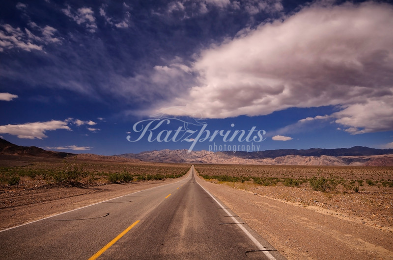 An empty highway crosses Death Valley National Park.