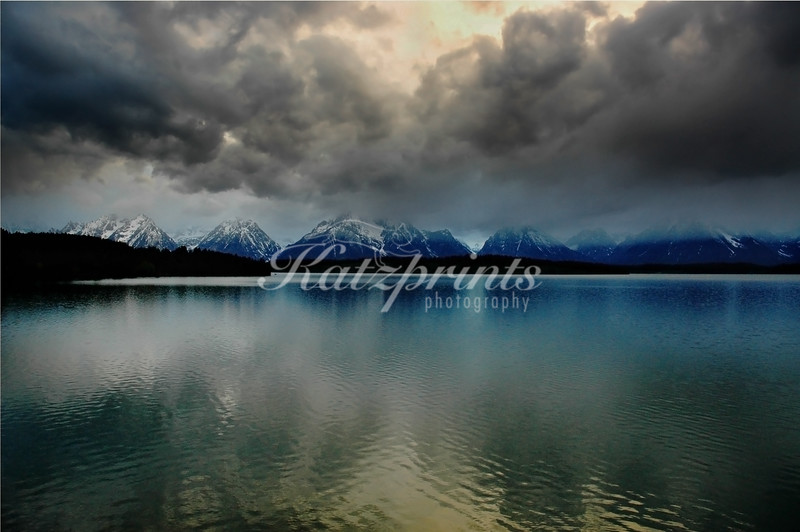 The clouds of an approaching snow storm are reflected in the calm waters of Oxbow Bend in Grand Teton National Park.