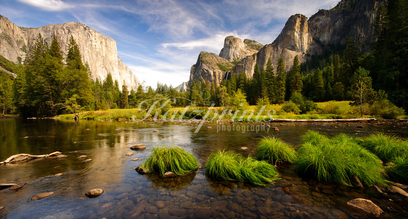 A calm Merced River flows through Yosemite Valley on an early autumn day.