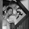 Bride and bridesmaids sneaking up the stairs