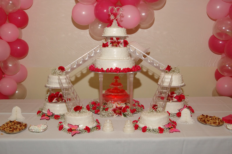 Huge and beautiful wedding cake with pink balloons surrounding.