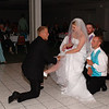 The groomsmen made a seat of knees for the bride while the groom removed her garter.